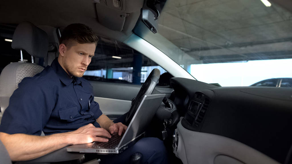 Male police officer working on laptop in car